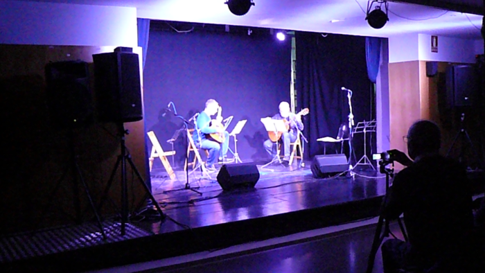 A room of the Centre Cultural Sanfeliu playing two gentlemen the guitar